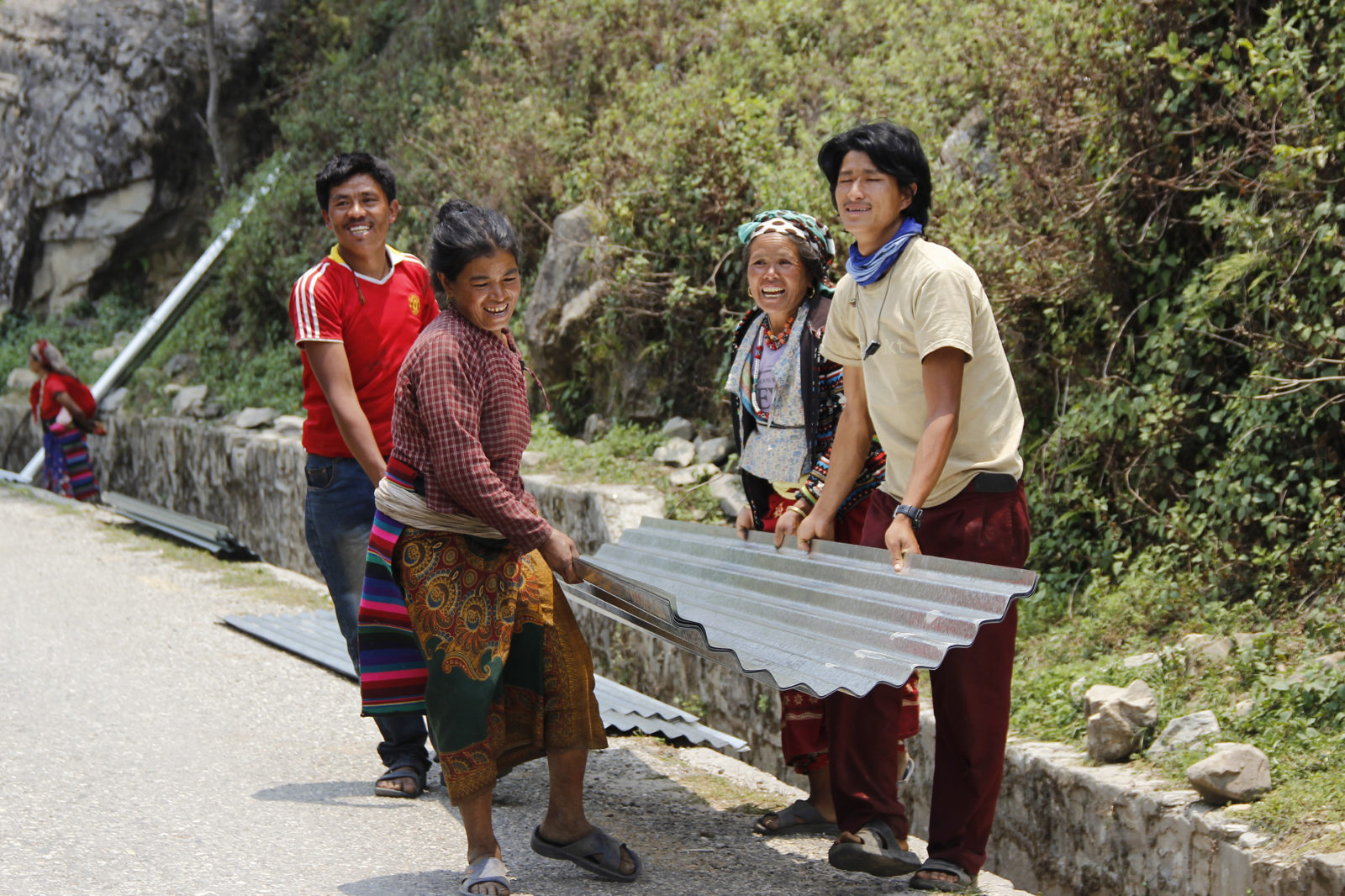 Twee maanden na de zware aardbevingen in april en mei, bouwen Nepalezen hun woningen op met nieuwe golfplaten.