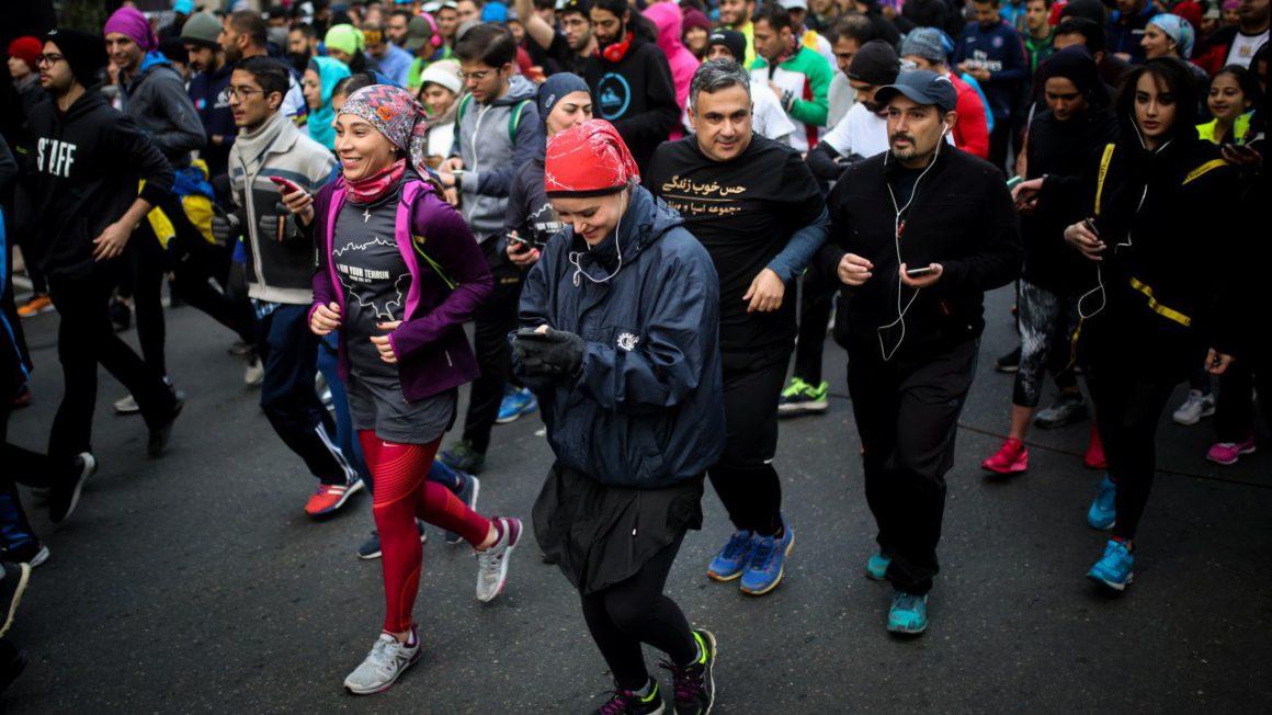Mannen en vrouwen lopen samen op vrijdagochtend in Teheran