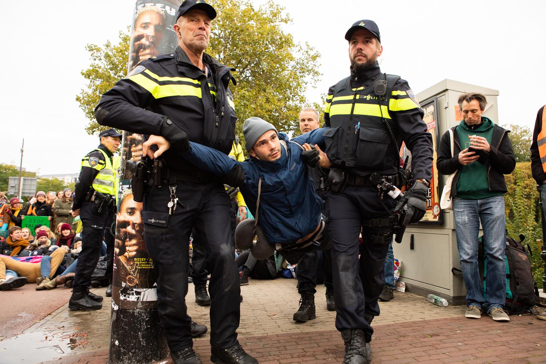Politie draagt demonstrant weg.