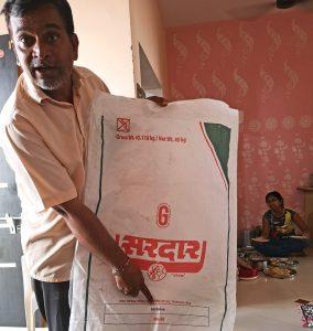 Katoenboer in Gujarat laat door de overheid goedgekeurde zak kunstmest zien
