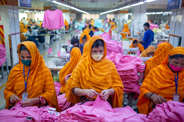 Garments workers are seen working in a sewing and finishing