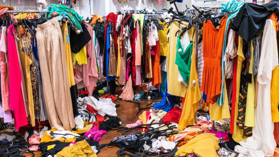 Colorful garments on racks and on the floor; fast fashion concept