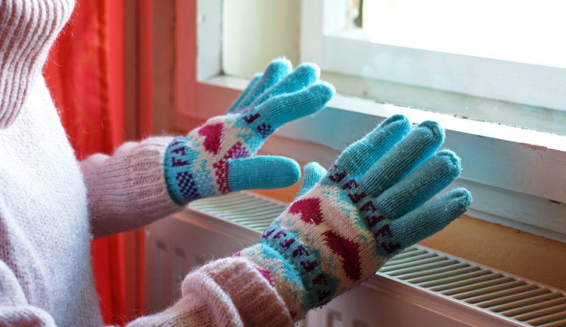 Hands in wool gloves on radiator