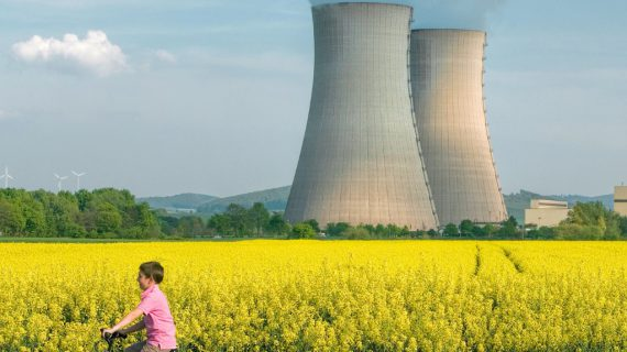 little-boy-cycling-in-front-of-nuclear-power-station-picture-id578801832