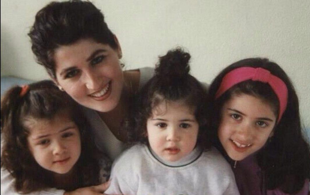Een vrolijk portret van Kosovare, vooraan in het midden, met haar twee oudere zussen en haar moeder in het azc in 1997.