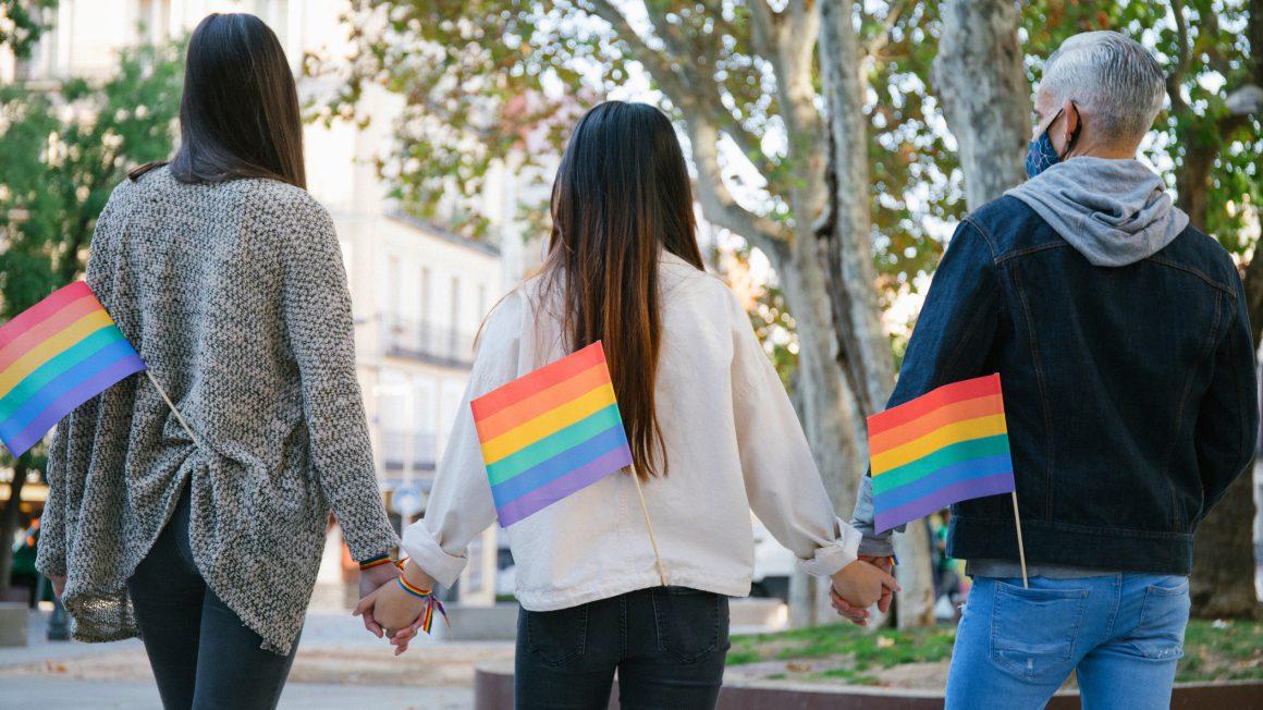 Drie mensen hand in hand op straat, op de rug gezien met LGBTIQ+-vlaggetje in hun achterzak.