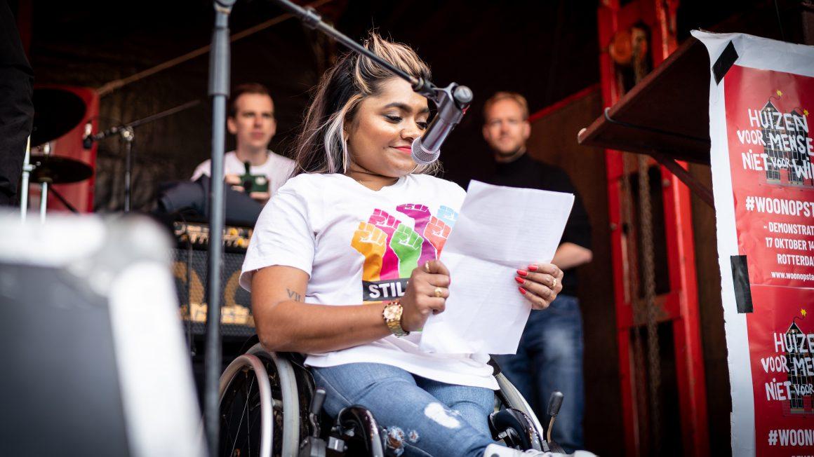 Een foto van Jeanette Chedda, enigszins van onderen genomen terwijl zij in haar rolstoel voor een microfoon zit. Ze draagt blauwe jeans en een wit T-shirt met kleurrijke opgestoken vuisten. Ze leest voor van een A4-papier.