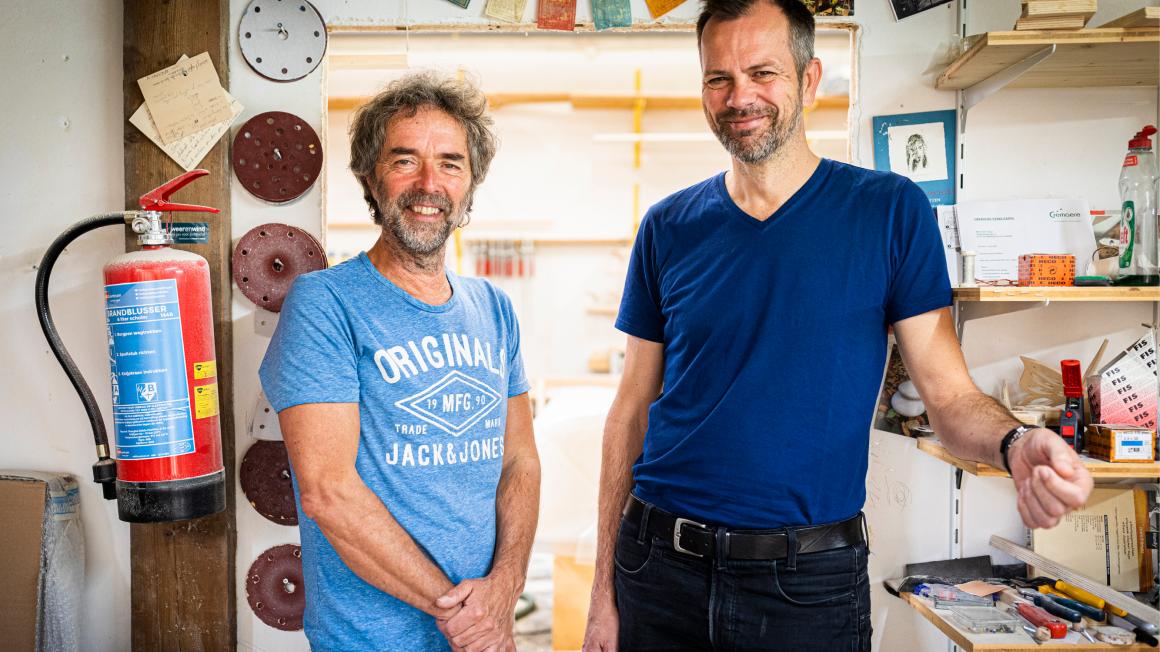 Radbout Spruit en Bart van Riet staan in een werkplaats. Links van hen hangt een brandblusser aan een pilaar. Achter hen schuurschijven en gereedschap.